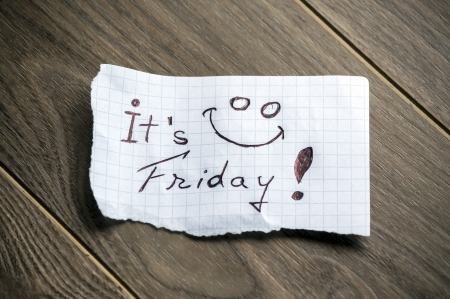It's Friday - Hand writing text on a piece of paper on wood background photo