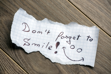 hand torn: Dont forget to Smile - Hand writing text on a piece of paper on wood background Stock Photo