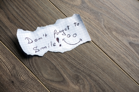 Dont forget to Smile - Hand writing text on a piece of paper on wood background with space for text photo