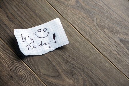 It's Friday - Hand writing text on a piece of paper on wood background with space for text