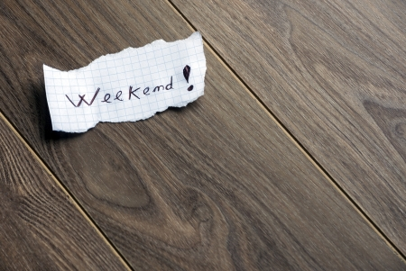 saturday: Weekend - Hand writing text on a piece of paper on wood background with space for text