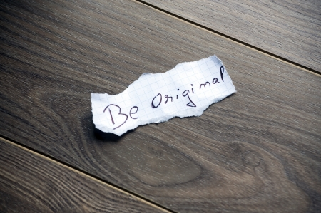 Be original written on piece of paper, on a wood background.