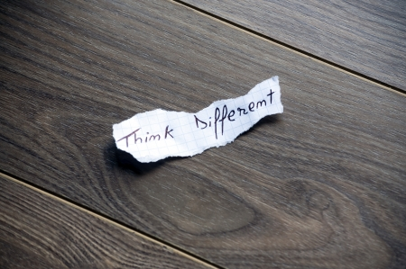 Think different written on piece of paper, on a wood background. photo