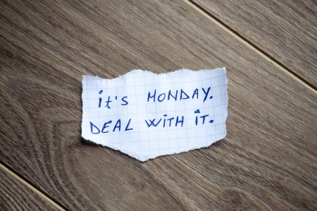 Its Monday. Deal With it written on piece of paper, on a wood background. photo