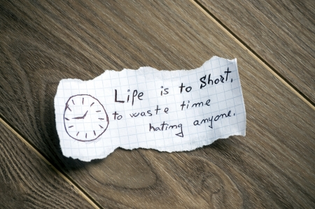 Motivational quote written on piece of paper, on a wood background. photo