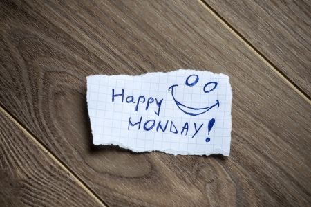 Monday message written on piece of paper, on a wood background. photo