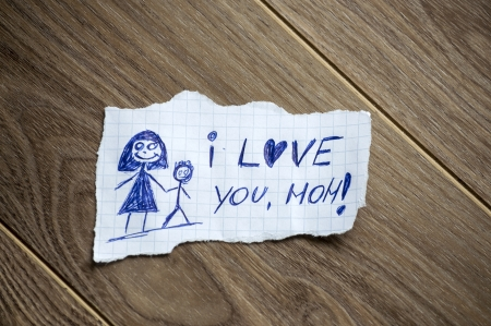 mom son: I love you, mom written on piece of paper, on a wood background Stock Photo