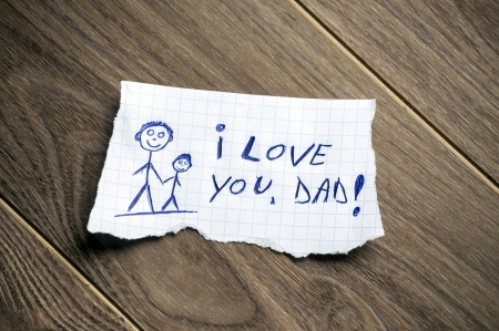 dad daughter: I love you, Dad written on piece of paper, on a wood background