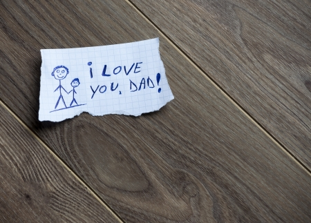 i kids: I love you, Dad,  written on piece of paper, on a wood background. Space for your text. Stock Photo