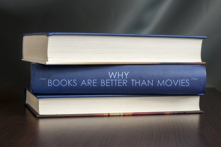 studious: Books on a table and one with  Why books are better than movies  cover. Book concept. Stock Photo