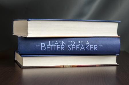 """marca libros: Los libros sobre una mesa y uno con """"aprender a ser un mejor orador."""" Cubierta. Concepto de libro."""