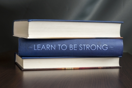 Books on a table and one with ' Learn to be strong. ' cover. Book concept. photo