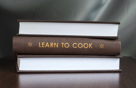 """Books on a table and one with """" Learn to cook. """" cover. Book concept."""