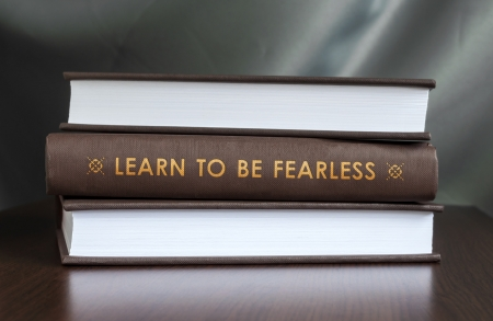 unafraid: Books on a table and one with  Learn to be fearless.  cover. Book concept. Stock Photo