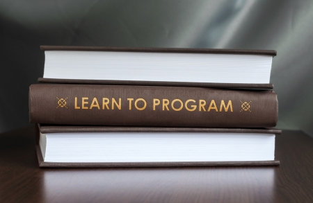 source code: Books on a table and one with  Learn to program  cover. Book concept.