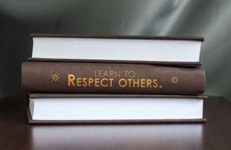 politeness: Books on a table and one with  Learn to respect others.  cover. Book concept.