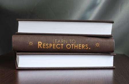 """respeto: Los libros sobre una mesa y uno con """"Aprender a respetar a los demás."""" Cubierta. Concepto de libro."""