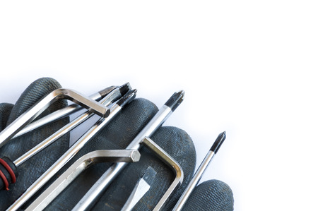unscrew: Set of screwdrivers and glove over a white background with space for text