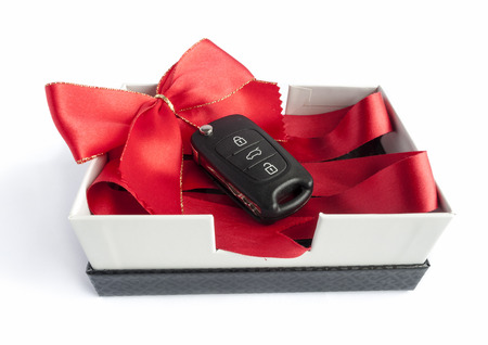 Black car key in a present box with a red ribbon Imagens