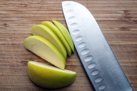steely: Close up detail of a large knife and a sliced green apple on a wood chopping board.