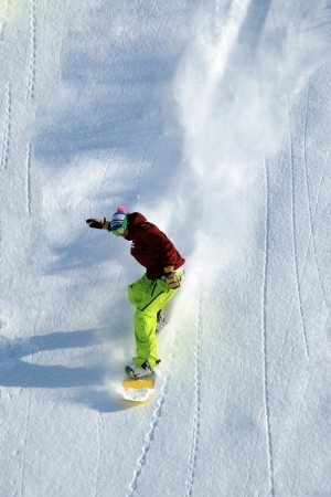 Freerider snowboarder moving down in snow powder  photo