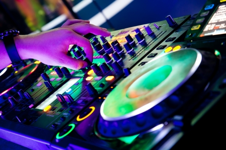 dj turntable: Dj mixes the track in the nightclub at a party