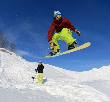 Jumping snowboarder against the blue sky photo