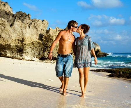 beach kiss: Young happy couple kissing during a walk along the coast