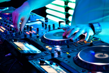 dj mixer: Dj mixes the track in the nightclub at a party