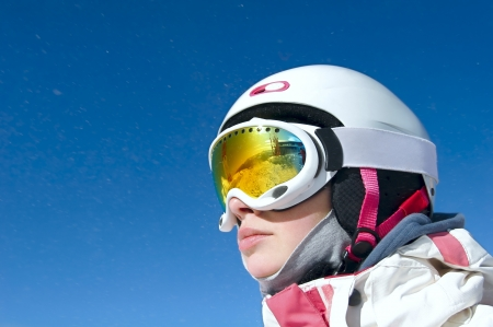 Portrait of a snowboarder at Krasnaya Polyana in the helmet and protective mask on background of blue sky photo