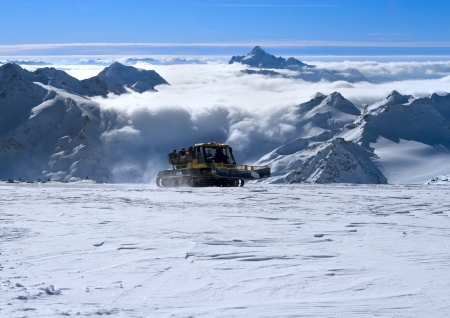 snow grooming machine: Snowcat with people going up the hill. The beautiful landscape of the Caucasus Mountains at Elbrus Stock Photo
