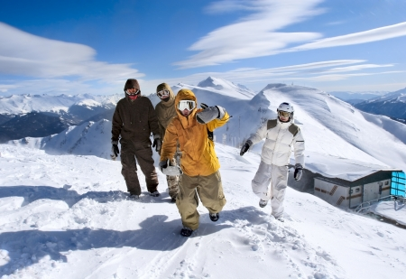 Snowboarders walking along the ridge of the mountains photo