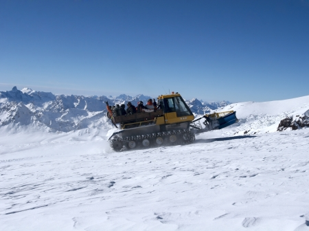 snowcat: Snowcat with people going up the hill. The beautiful landscape of the Caucasus Mountains at Elbrus Stock Photo