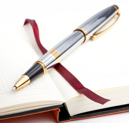 Notebook with bookmark and pen on a white background