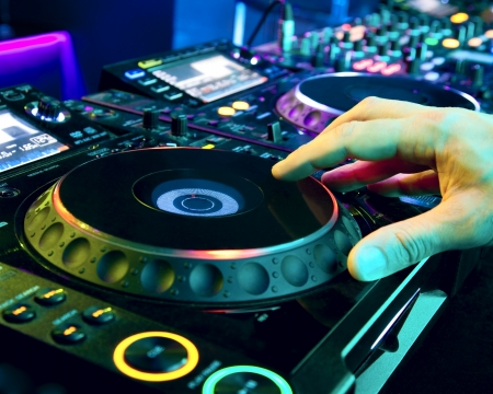 Dj mixes the track in the nightclub at a party photo