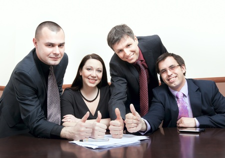 Happy business people with thumbs up at a conference. Business concept