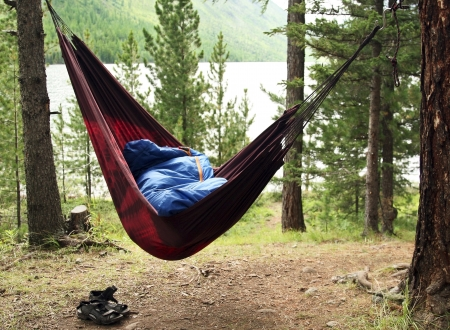 sleeping bag: Man sleeps in a hammock and in a sleeping bag early in the morning Stock Photo