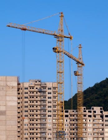 Cranes and building under construction on the skyline in mountainous terrain Stock Photo - 19381539