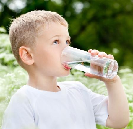 Child drinking pure water in nature Standard-Bild