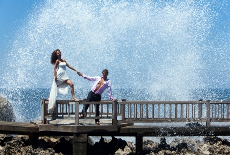 love in rain: Happy young couple walking on the old pier  Ocean waves beating on the rocks Stock Photo