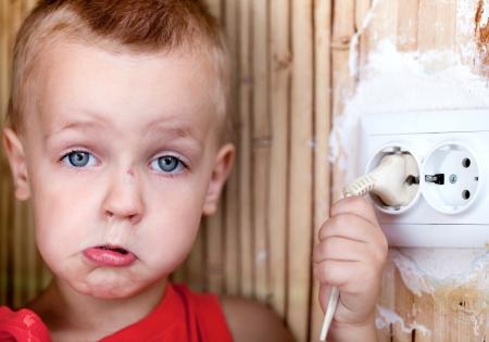 enchufe: Niño pequeño que tira de la cuerda de la toma eléctrica