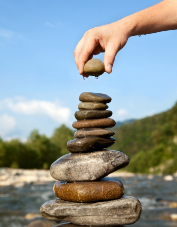 stacked stone: Man s hand puts Pyramid of stones Stock Photo