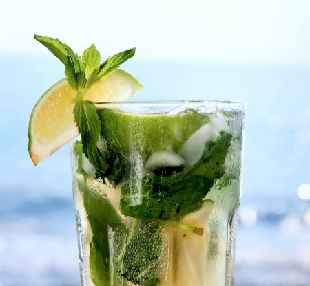 Cocktail mojito ice lemon on the background of the ocean photo