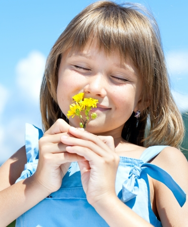freckled: Happy little girl with eyes closed, smelling flowers in his hand against the blue sky