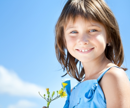 freckled: Happy young girl with a flower in his hand against the blue sky