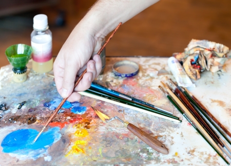 Hand of the artist with a paintbrush and Artistic equipment: paint, brushes, spatula and art palette photo