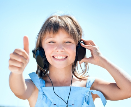 Happy little girl in headphones listens to music against the blue sky photo