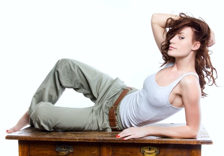commode: Portrait attractive beautiful woman lies on the old cabinet on white background