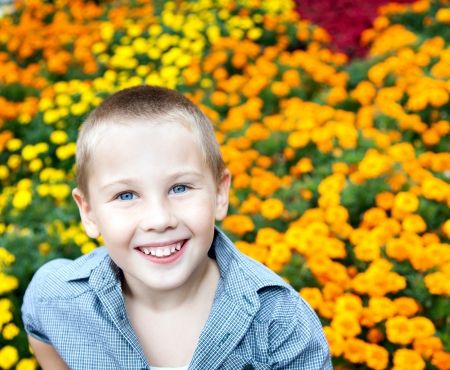 combed: Portrait of beautiful young boy with blue eyes  on background variety of flowers in the park