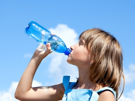 freckled: Attractive young beautiful girl drinking water from plastic bottles